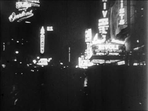 B/W 1928 car point of view past neon signs for theaters + nightclubs at night / newsreel