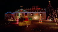 Car point of view past suburban house with Christmas lights at night