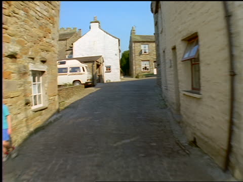 Car point of view through narrow village streets / Village of Dent / Yorkshire Dales / England