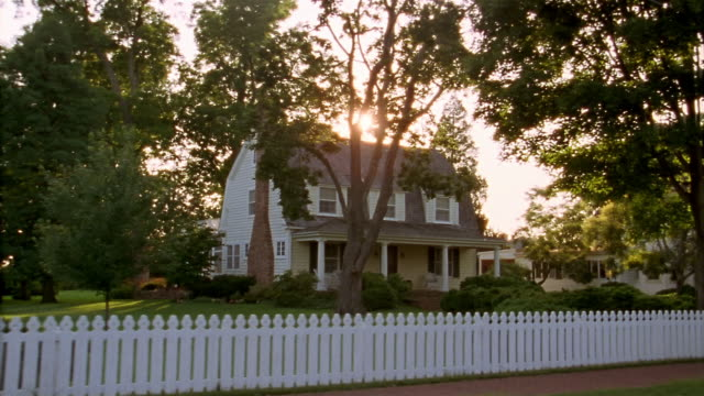 Car point of view wide shot driving by house with white picket fence in suburban neighborhood / sun shining / Maryland