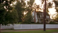 Car point of view wide shot driving by houses with white picket fences in suburban neighborhood / sun shining / MD