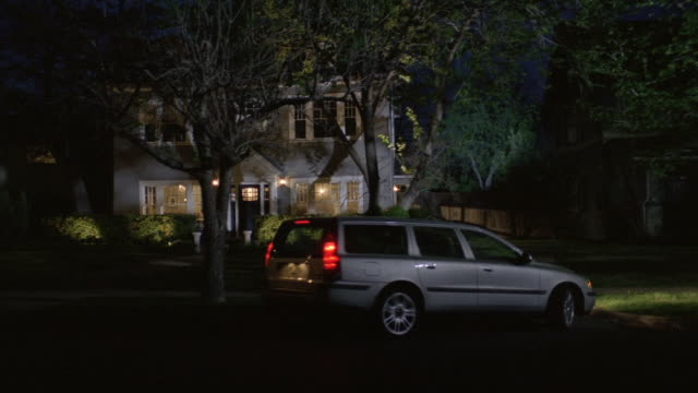 WS Car pulling into driveway in front of large home at night / United States