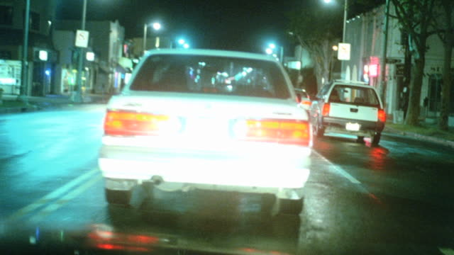 CAR Car pulling out into traffic in light industrial area passing cars close to back bumpers weaving though light traffic