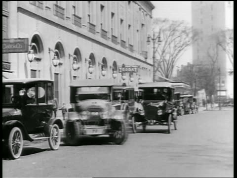 B/W 1919 car pulling out of parking space without looking + almost gets hit by other car / newsreel