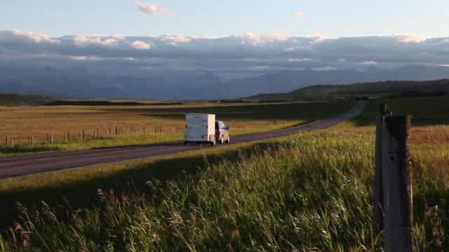 Car pulling trailer drives down rural road towards mtns