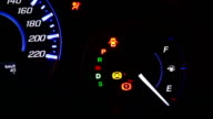 Car speedometer and fuel gauge on dashboard at night