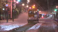 A car speeds past a snow-removal vehicle as it sweeps snow off the streetcar line in Sapporo, Japan.