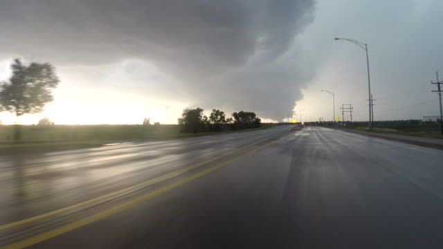 Car POV of storm chasers driving down Route 283 and entering the south side of Dodge City KS as a large tornado visible on the horizon tears up the...