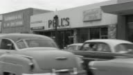 1955 B/W MONTAGE POV Car travelling down suburban streets / El Monte, California