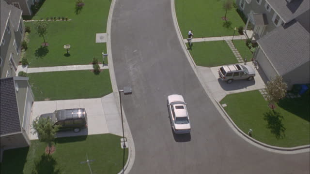 A car turns down a suburban street and into a driveway.
