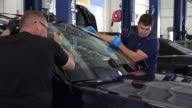 Car windshield is installed by two workers at a garage in Chattanooga TN NO