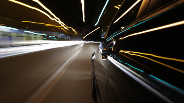 MS T/L POV Car with left rear mirror in middle ground driving through city during night / Munich, Bavaria, Germany