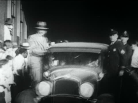 B/W 1930 car with police standing on sideboards pulling up to camera