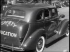 B/W 1938 REAR VIEW car with 'Safety Education' lettering driving on street away from camera