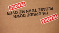 Cardboard box with 'this way up' message and fragile stickers, UK
