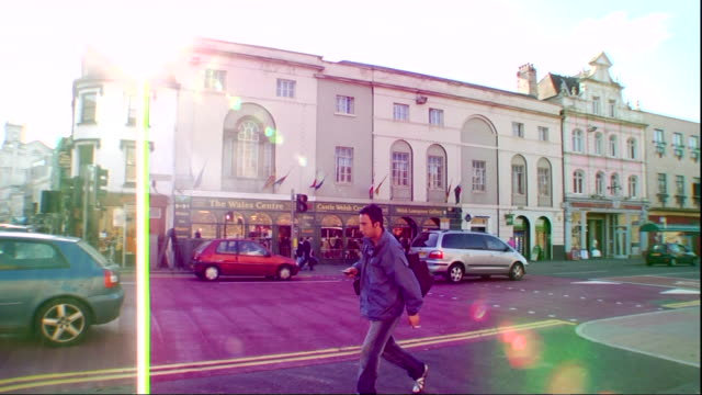 Cardiff city centre street unidentifiable people crossing FG various stores lined up along street BG slight sun glare of frame UK