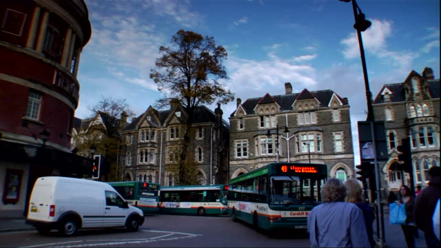 Cardiff city centre street unidentifiable people walking on street buses making turn passing toward frame multistory houses BG Capital City of Wales...
