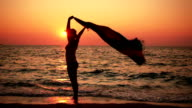 Carefree Woman On The Beach Holding Scarf At Sunset