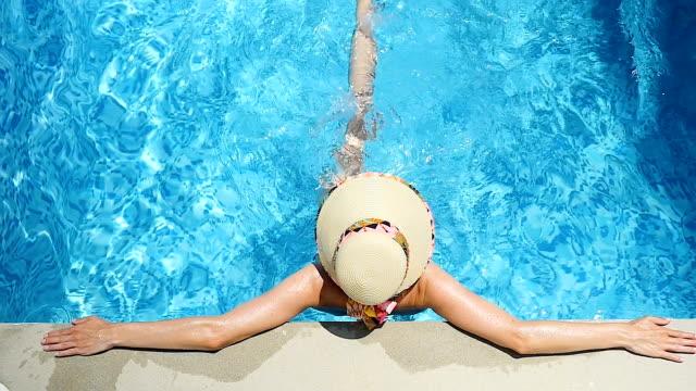 Unbeschwerte Frau entspannen Sie im Pool & treten das Wasser