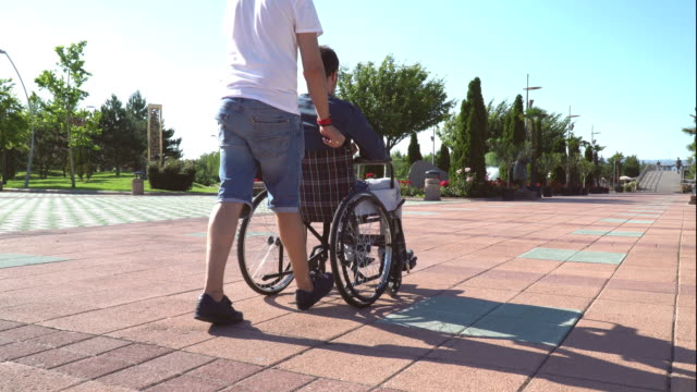 Caregiver And Young Man On A Wheelchair Walking Outdoors