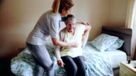 Caregiver Helping Senior Woman Dress