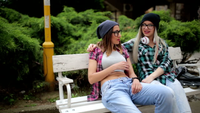 Careless girlfriends laughing at the park on the bench