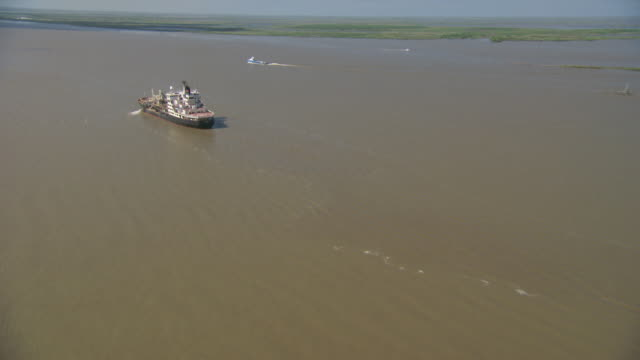 AERIAL WS Cargo ship flowing on river with helipad / New Orleans, Louisiana, United States