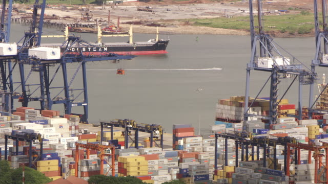 MS cargo ship passes by shipping containers on dock on the Panama Canal / Panama