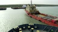 A cargo ship slowly cruises through a bay.