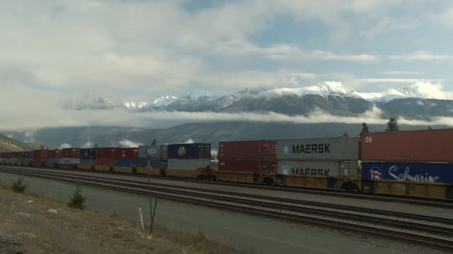 WS Cargo train with snow capped mountains covered with clouds lit by morning light / Jasper, Alberta, Canada