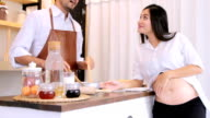 Caring husband preparing food in kitchen for pregnant wife.HD format.