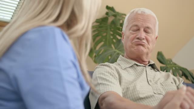 HD DOLLY: Caring Nurse Talking With Senior Man