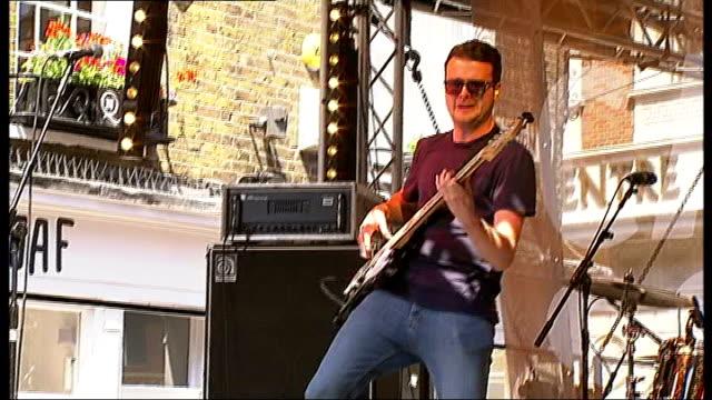 Carnaby Street festival **Music heard SOT** Band performing Men playing ukelele **Vox pops partly overlaid SOT** Hand strumming ukelele