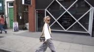 Caroline Daur wears sunglasses striped flared pants white shoes an off shoulder top outside JW Anderson during London Fashion Week September 2017 on...