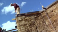 MS Carpenter adjusting threaded rod compressing straw bale used to form house wall, Grass Lake, Michigan, USA