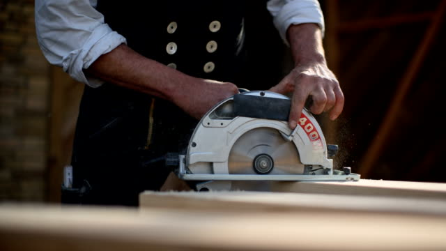 Carpenter at work with the portable circular saw