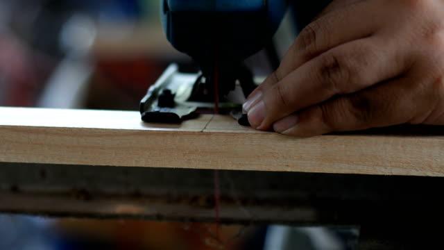 Snickare sågning av trä med sticksåg cutter i hem workshop