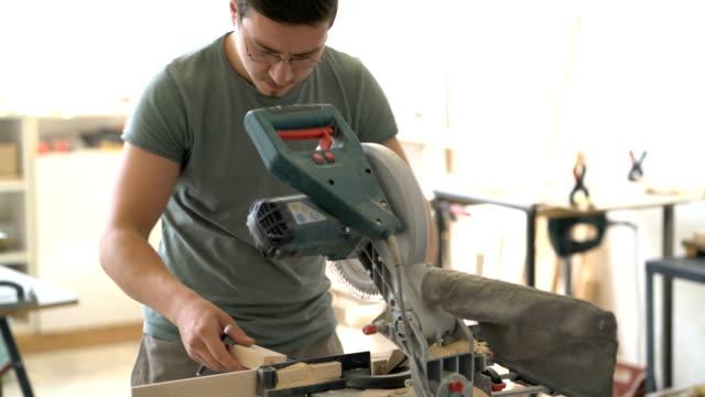 Carpenter cutting wooden board on the circular saw machine in his carpenter workshop.
