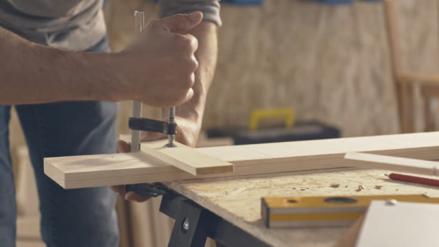 Carpenter removing clamp from pieces of wood