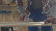 Carpenter sanding wood block in workshop