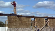 WS Carpenter working on top of wall of straw house under construction, Grass Lake, Michigan, USA