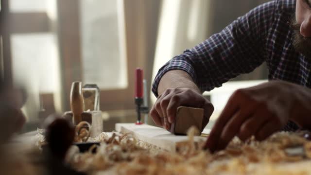 Carpentiere lavora con carta vetrata