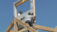WS ZO Carpenters and crane operator placing window frame while framing an energy efficient post / Grass Lake, Michigan, USA