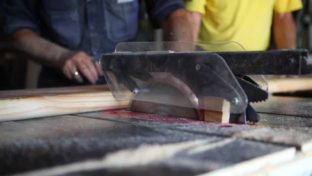Carpenters hard at work cutting wood