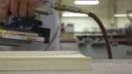 Carpenters use power sanders on large pieces of wood at a furniture manufacturing workshop operated by Northland Furniture in Bend Oregon An...