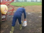 Carrot pesticide scare ITN Midlands MS Man in blue overalls walks PAN LR carrying bags pesticide past tractor BV Man walks away puts down pesticides...