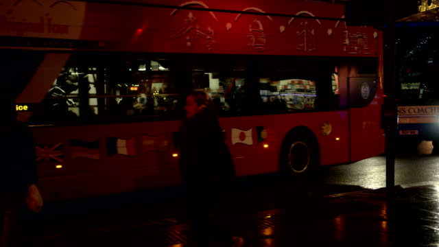 Cars and buses pass by at Piccadilly Circus in London in slow motion at night