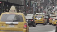 Cars and cyclists pass on a busy Manhattan street