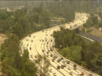 Cars and lorries travel along s-bend of tree lined busy highway Los Angeles