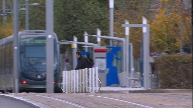 Pan Left Bicycles crossing the tracks A streetcar starts running Medium Shot